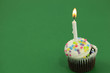 Birthday cupcake on green background