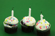 three birthday cupcakes with candles blown out