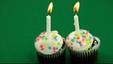 Two birthday cupcakes with candles burning