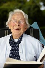 Nette alte Dame mit Buch lachend