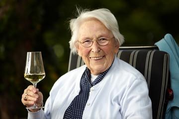 Nette alte Dame mit Wein lachend
