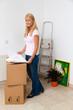 Frau mit Plan in neuer Wohnung beim Umzug.