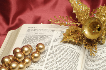Bible open to  Luke 2 with gold Christmas decorations
