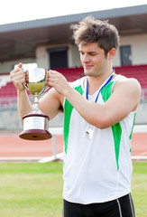 Sporty man holding a cup and a medal standing
