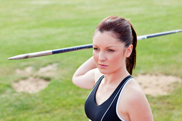 Determined female athlete ready to throw javelin