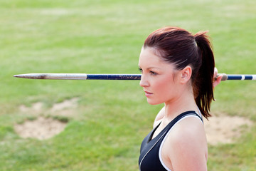 Concentrated athletic woman ready to throw the javelin