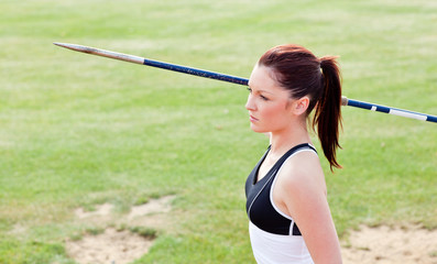 Concentrated female athlete ready to throw javelin