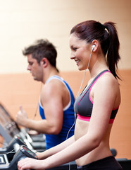 Young athletes exercising on a running machine with earphones
