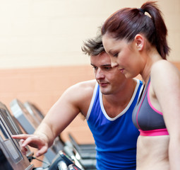 Pretty athletic woman standing on a running machine with her per