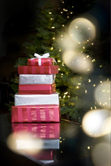 christmas presents on table - tree in background, lights bokeh f