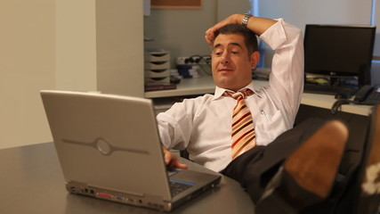 Relaxed businessman using laptop in office