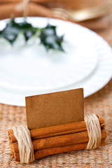 aromatic place card with holly twig in white plate
