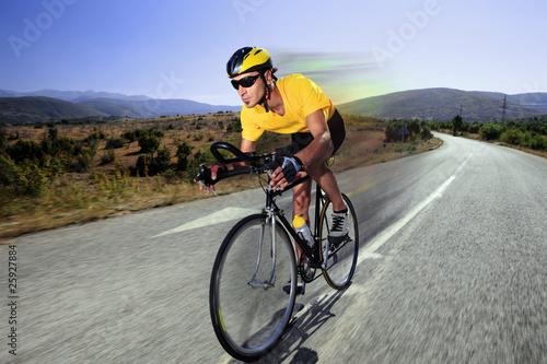 Fotobehang Wielersport Cyclist riding a bike on an open road