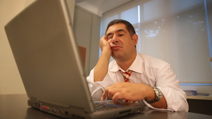 Tired businessman using laptop in office
