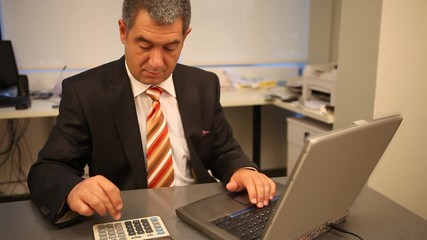 Businessman working on laptop in office, calculating