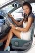 Beautiful woman sitting in car short dress