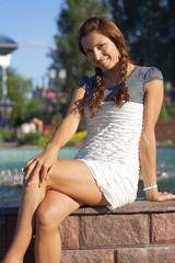 Beautiful woman sitting on fountain background