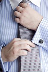 Businessman straightening his necktie