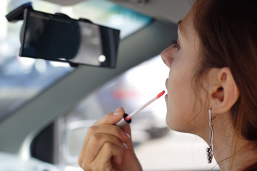 Beautiful Woman do put on make-up in car