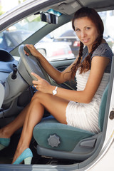 Beautiful woman sitting in car short dress