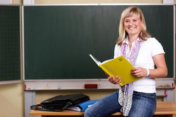 junge Lehrerin mit Klassenbuch