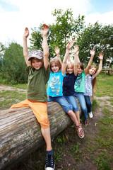 Kinder auf Baumstamm