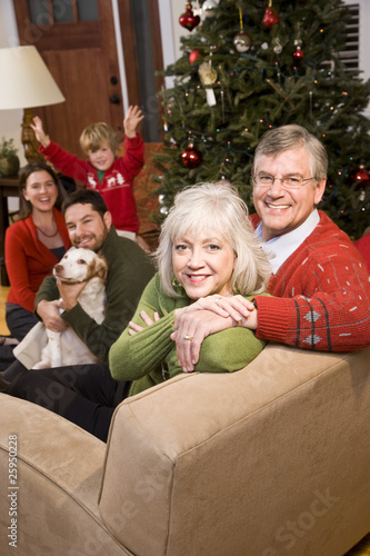 Senior couple with family by Christmas tree