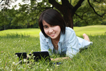 A smiling young girl with laptop outdoors
