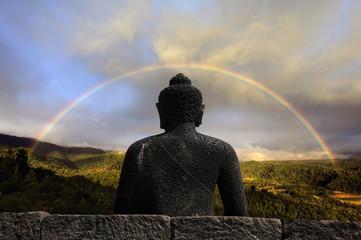 Buddha coverend under a full rainbow