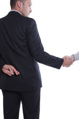 Businessman with fingers crossed behind shaking hands