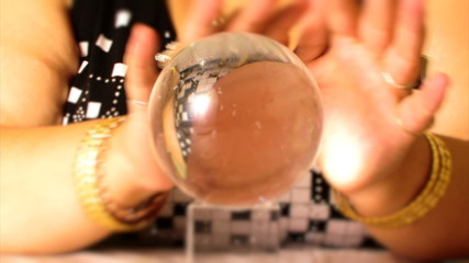 fortuneteller moves hands around magic crystal ball