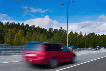 Fast driving red car on high way - motion blur