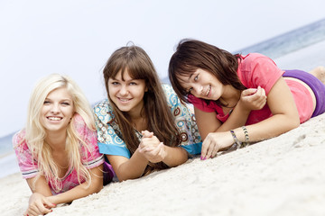Three girlfriends lying down at the beach.