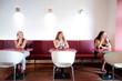 Three women in restaurant looking through window