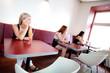 Three women in restaurant looking away, tilted