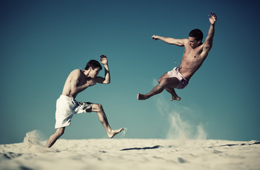Two young men sport fighting on beach