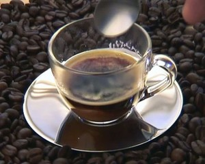 Sugaring black coffee over a coffe bean background.