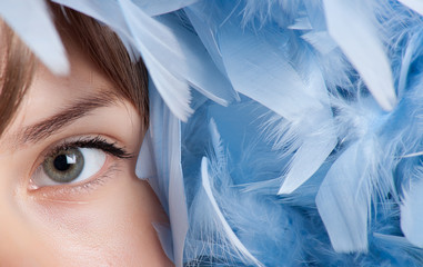 Girl posing with blue feathers
