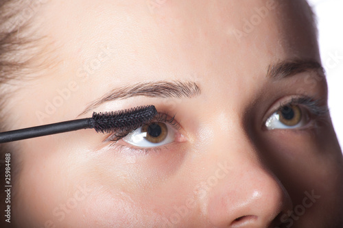 Beautiful woman putting make up on eye