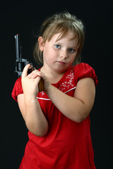 Small girl with toy gun looking dangerous on black