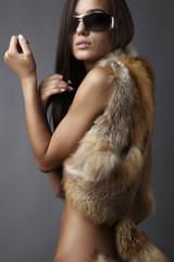 stylish brunette in fox cape and sun glasses.