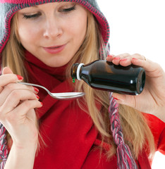 young woman in winter hat with spoon of syrup