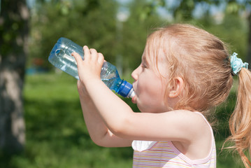 A little girl is drinking clean water from a bottle