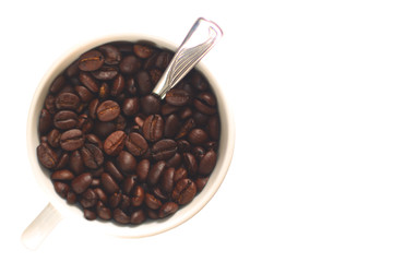 Coffee cup filled with coffee beans and a spoon