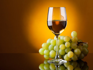 A glass of white wine and a bunch of green grapes