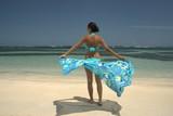 Fototapety Femme sur une plage avec un paréo bleu
