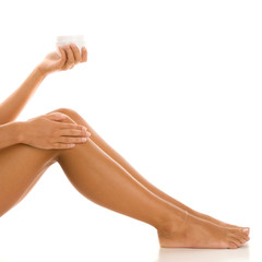 Woman applying cream on legs