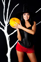 slender girl dressed as a witch holding a pumpkin at the tree at