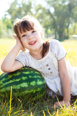 A little girl lies on watermelon