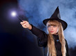 Girl in witch's hat with magic wand.